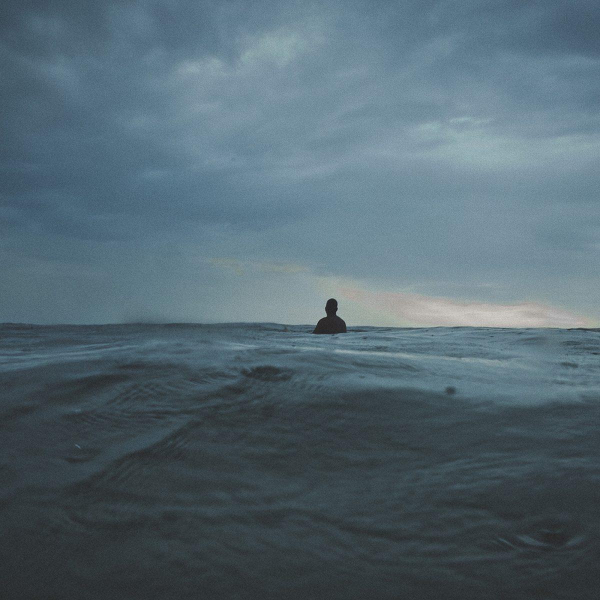 Surfista solitário sentado sobre a prancha no outside espera a série olhando para o horizonte sob um céu nublado