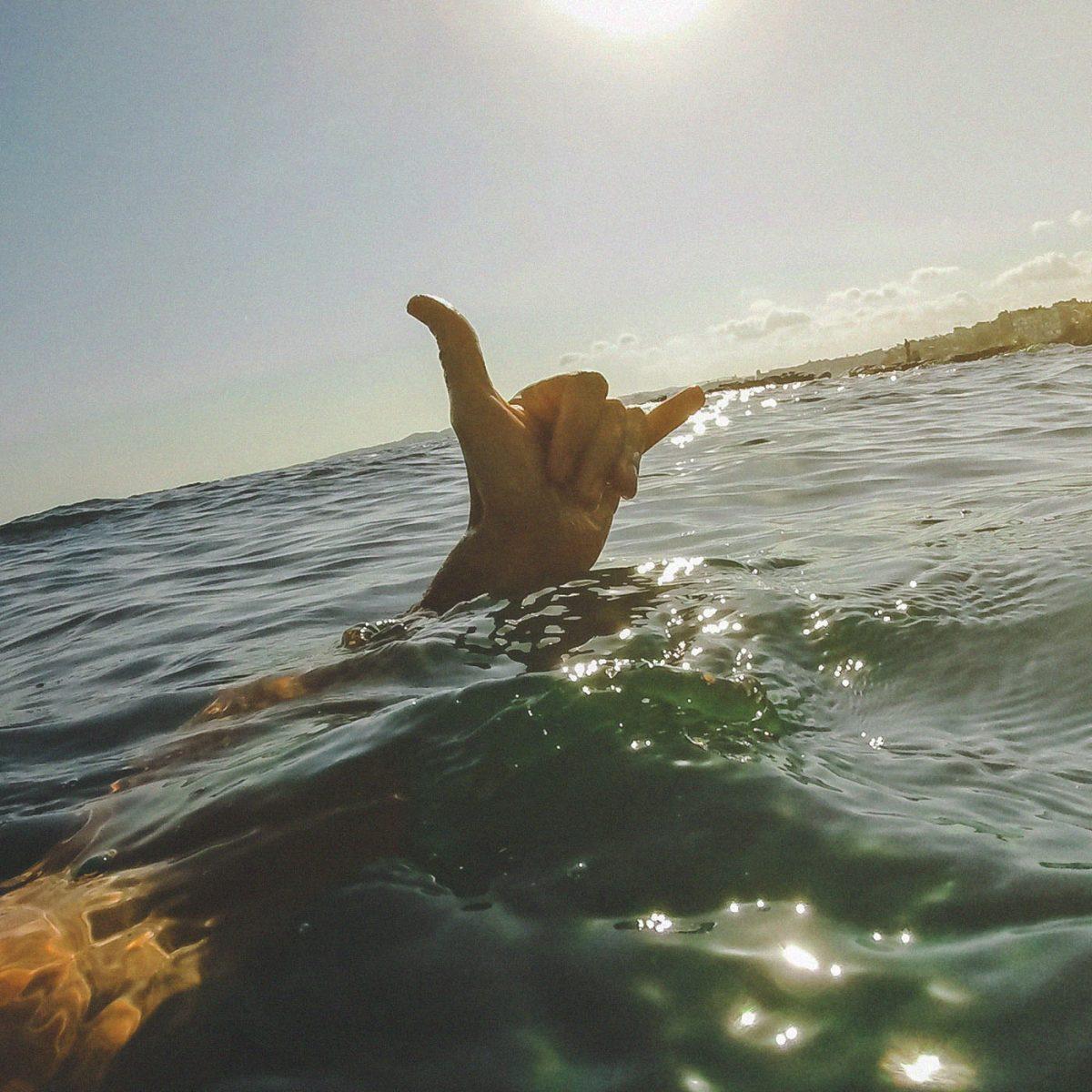 Mão de surfista profissional fazendo sinal de shaka brah dentro do mar